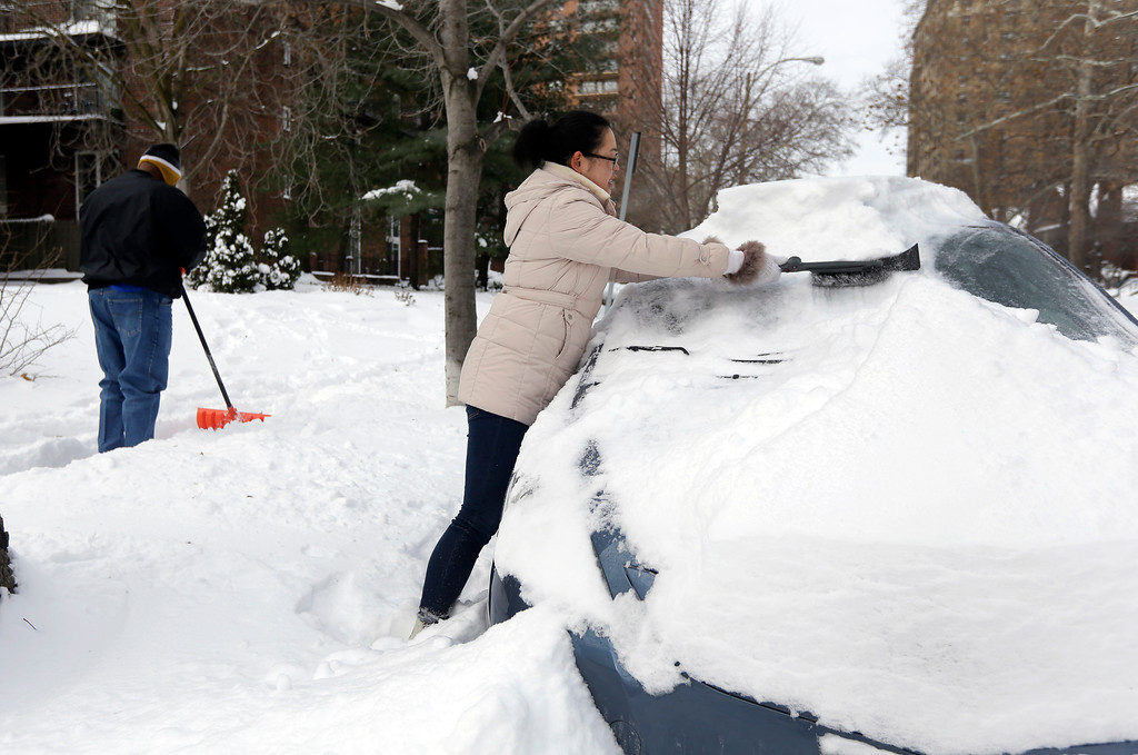 . Cecy Wang, right, clears snow off her car as Samuel Scott, left, shovels a sidewalk Tuesday, Jan. 7, 2014, in St. Louis. As Missourians muddled through another frigid day Tuesday, the worst cold snap in nearly two decades was about to come to an end but many roads remained partly snow-covered two days after a winter storm dumped several inches of snow. (AP Photo/Jeff Roberson)