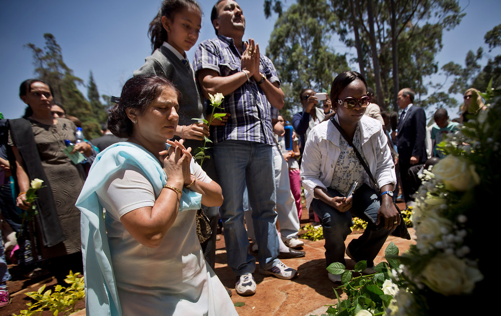 Description of . Relatives of those who died lay white roses and pray at a stone memorial, during a memorial service marking the one-month anniversary of the Sept. 21 Westgate Mall terrorist attack, in Karura Forest in Nairobi, Kenya Monday, Oct. 21, 2013.  (AP Photo/Ben Curtis)