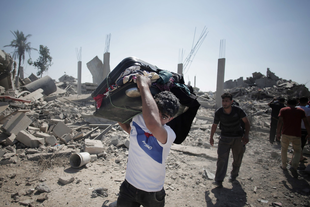 Description of . Palestinians salvage what they can from their belongings in the village of Khuzaa, southern Gaza Strip, Friday, Aug. 1, 2014. A three-day Gaza cease-fire that began Friday quickly unraveled, with Israel and Hamas accusing each other of violating the truce. (AP Photo/Khalil Hamra)