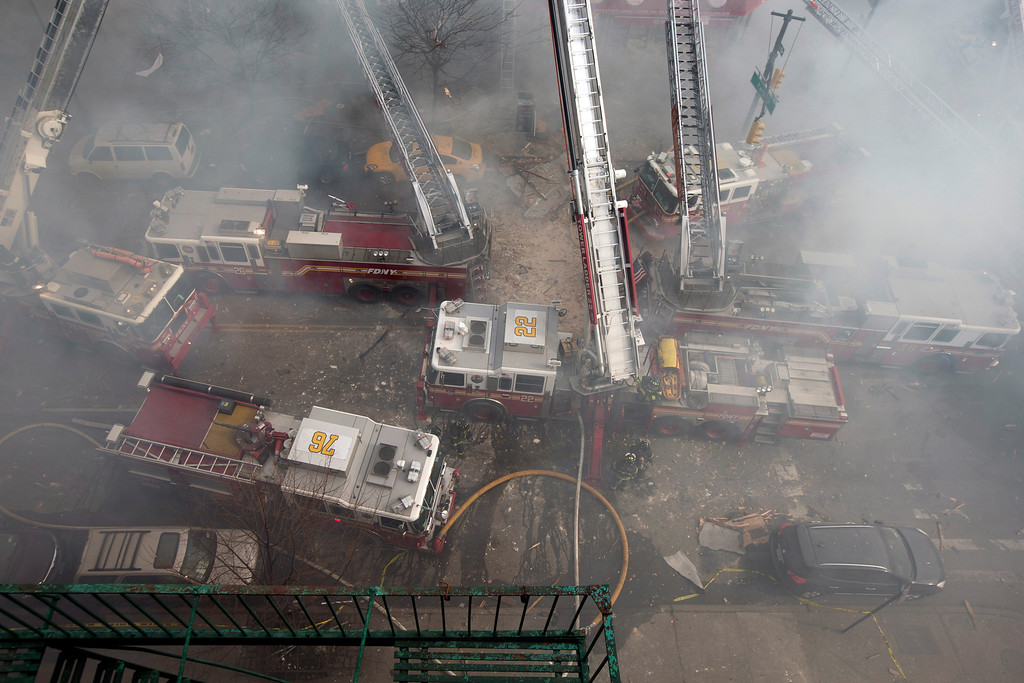 Description of . Firefighters respond to a fire on 116th Street in Harlem after a building exploded in huge flames and billowing black smoke, leading to the collapse of at least one building and several injuries, Wednesday, March 12, 2014, in New York. (AP Photo/John Minchillo)