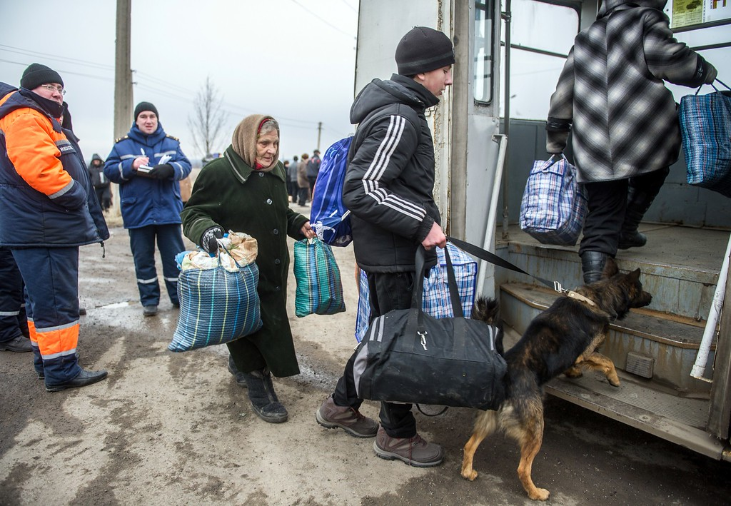 Description of . Refugees from Debaltseve get into buses in Artemivsk to escape the pro-Russain rebels shelling on February 5, 2015. German Chancellor Angela Merkel and French President Francois Hollande touched down in Kiev today with a new peace plan to stop an upsurge in fighting in east Ukraine. VOLODYMYR SHUVAYEV/AFP/Getty Images