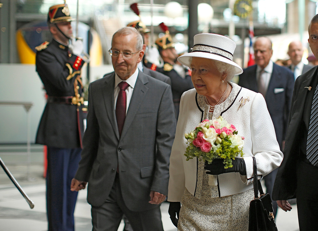 Description of . Britain's Queen Elizabeth arrives at the Gare du Nord train station in Paris, France, to start a three-day state visit to France, Thursday, June 5, 2014. The Queen and her husband Prince Philip are in France for a three-day state visit to mark the 70th anniversary of the D-Day landings. Unidentified official at left. (AP Photo/Benoit Tessier, pool)