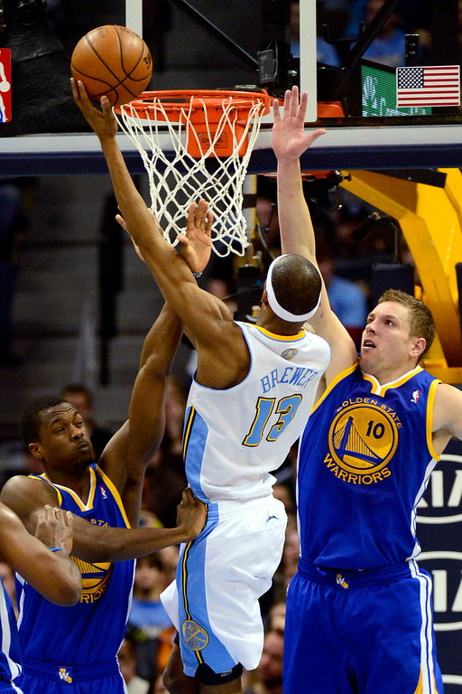 Description of . Denver Nuggets small forward Corey Brewer (13) drives against Golden State Warriors power forward David Lee (10) during the second half of the Nuggets' 116-105 win at the Pepsi Center on Sunday, January 13, 2013. AAron Ontiveroz, The Denver Post