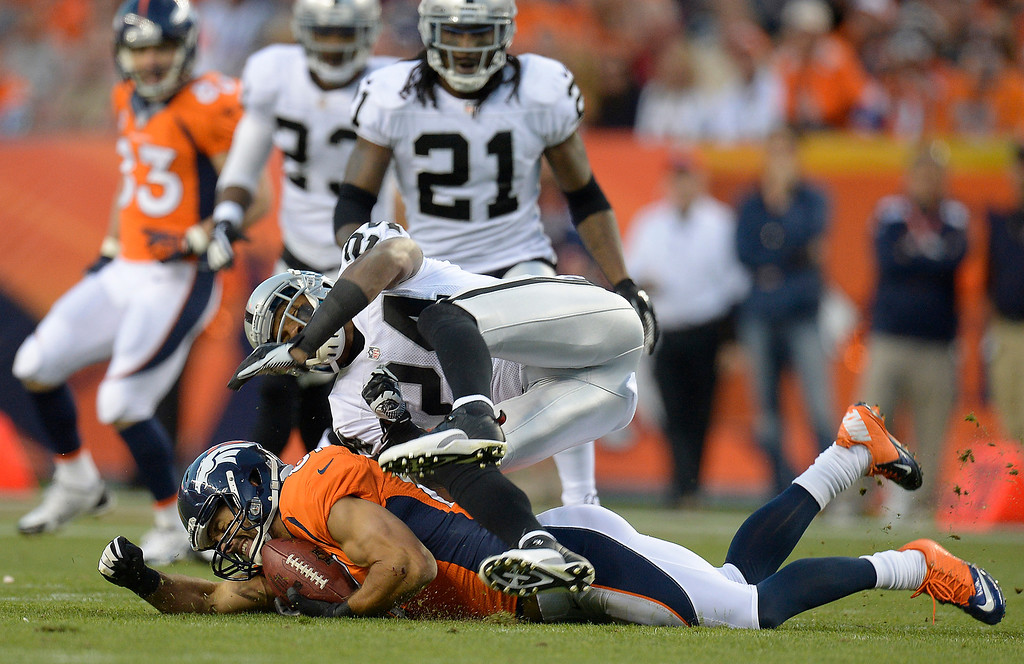 Description of . Denver Broncos wide receiver Eric Decker (87) gets tackled in the first quarter. The Denver Broncos took on the Oakland Raiders at Sports Authority Field at Mile High in Denver on September 23, 2013. (Photo by John Leyba/The Denver Post)