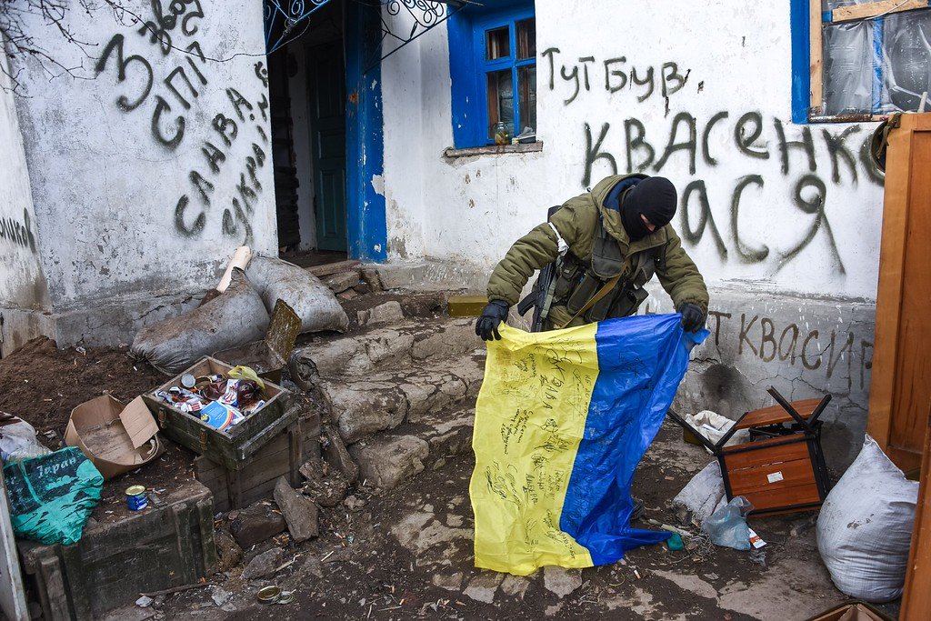 Description of . A pro-Russian rebel holds a Ukrainian flag found in a check-point captured by pro-Russian rebels, at the town of Krasniy Partizan, eastern Ukraine, Saturday, Jan. 24, 2015. The fighting continues despite several cease fire declarations. (AP Photo/Mstyslav Chernov)