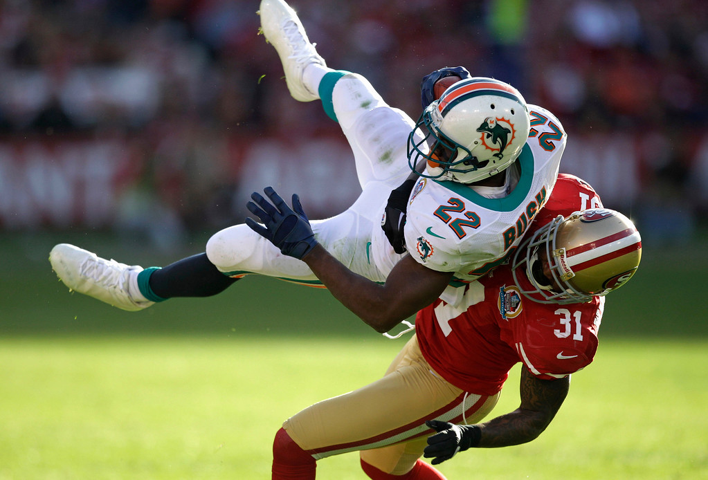 Description of . Miami Dolphins running back Reggie Bush, left, is stopped with the ball by San Francisco 49ers strong safety Donte Whitner, right, during the third quarter of an NFL football game in San Francisco, Sunday, Dec. 9, 2012. (AP Photo/Ben Margot)
