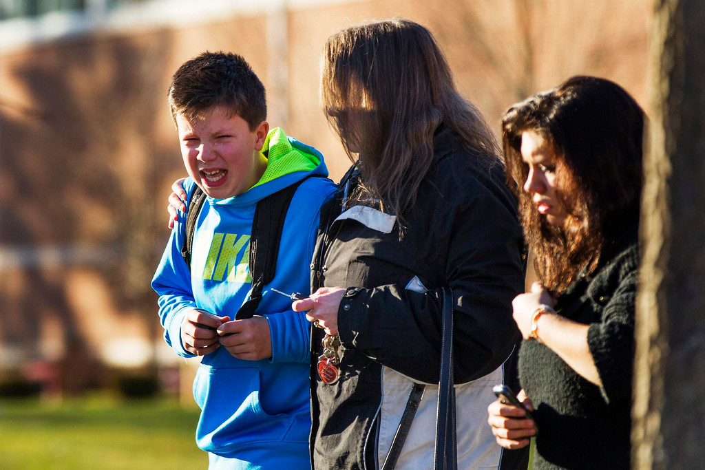 Description of . A boy weeps as he is told what happened after being picked up at Reed Intermediate School following a shooting at Sandy Hook Elementary School in Newtown, Connecticut, December 14, 2012. A heavily armed gunman opened fire on school children and staff at a Connecticut elementary school on Friday, killing at least 26 people, including 18 children, in the latest in a series of shooting rampages that have tormented the United States this year. REUTERS/Lucas Jackson