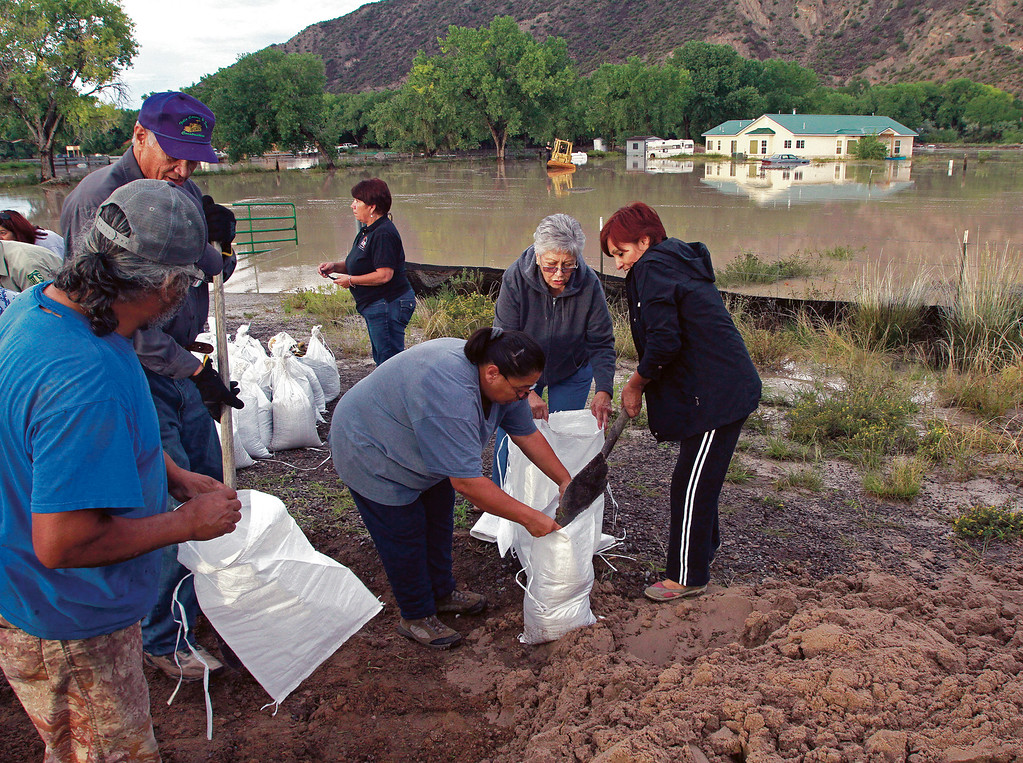 Description of . Residents make sandbags to help out their neighbors that were flooded out in Chili, N.M.,  about 5 miles north of EspaÒola,  on Wednesday, Sept. 18, 2013.  It could be a while before the exact amount of damage from recent heavy rain and flooding in New Mexico will be known, officials said.  Counties are submitting preliminary flood damage estimates to the Federal Emergency Management Agency as federal officials work to tally their own assessment, a process that may take weeks.  (AP Photo/The Santa Fe New Mexican, Jane Phillips)