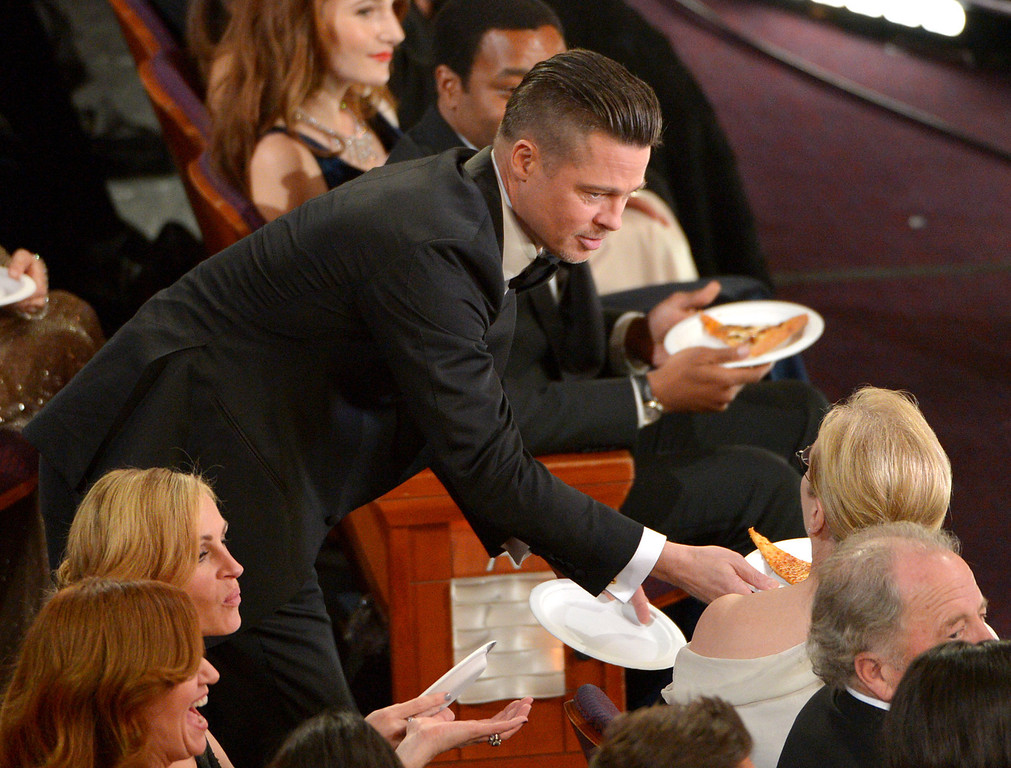 Description of . Brad Pitt, left, shares pizza with Meryl Streep in the audience during the Oscars at the Dolby Theatre on Sunday, March 2, 2014, in Los Angeles.  (Photo by John Shearer/Invision/AP)