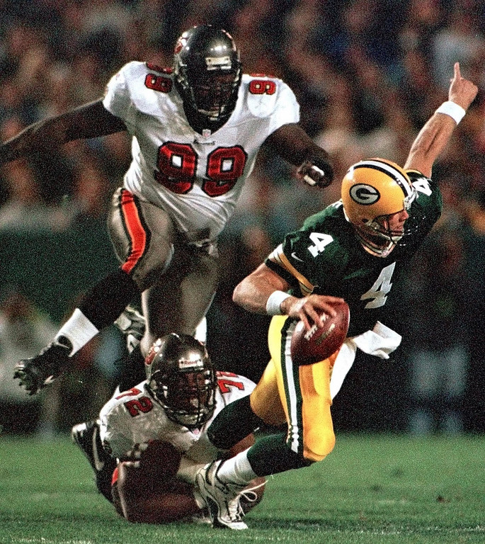 Description of . Green Bay Packers quarterback Brett Favre (4) gets away from Tampa Bay Buccaneers Chidi Ahanotu (72) and Warren Sapp (99) to complete a pass in the first quarter Sunday night, Oct. 10, 1999, in Green Bay, Wis. (AP Photo/Andy Manis)