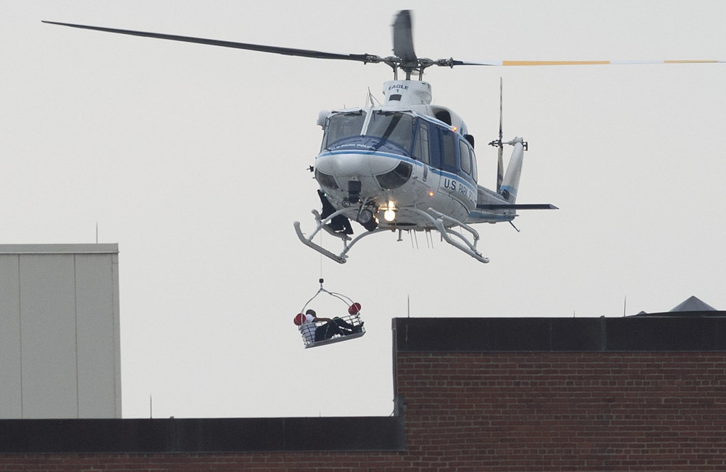 Description of . A helicopter lifts a person off the roof as police respond to the report of a shooting at the Navy Yard in Washington, Dc on September 16, 2013.  Departures have been halted at Washington's Reagan National Airport due to a shooting at the US Navy Yard, an official said Monday. Chris Paolino, a spokesman for the airport, said inbound aircraft are still landing and that the airport remains open to passengers.
