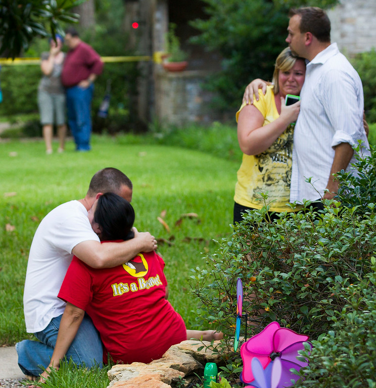 Description of . Neighbors embrace each other following a shooting Wednesday, July 9, 2014, in Spring, Texas. Deputies have cornered a man suspected in a shooting at a suburban Houston home that resulted in multiple fatalities. (AP Photo/Houston Chronicle, Brett Coomer)