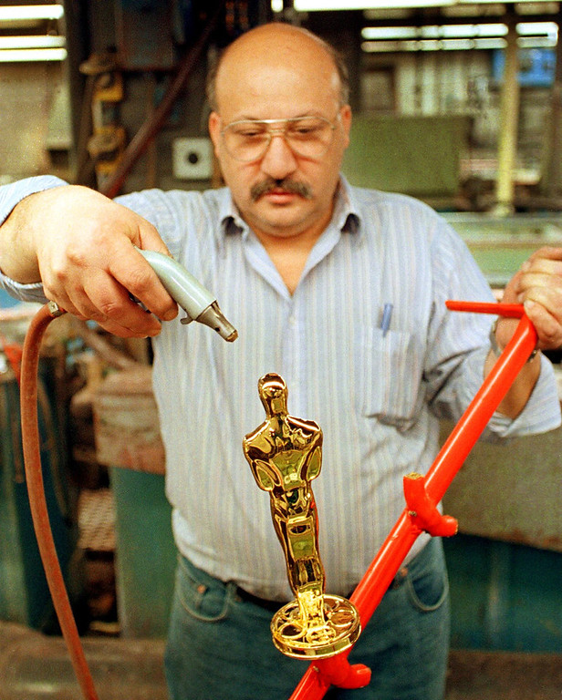 Description of . Nunzio Giganti uses a compressed air sprayer to dry an Oscar statuette after pulling it from a gold-plating solution at R.S. Owens in Chicago, Illinois, 02 February. The statuettes are cast, polished and plated with copper, nickel, silver and then gold in preparation for the upcoming Academy Awards to be presented in Los Angeles 21 March.   JOHN ZICH/AFP/Getty Images