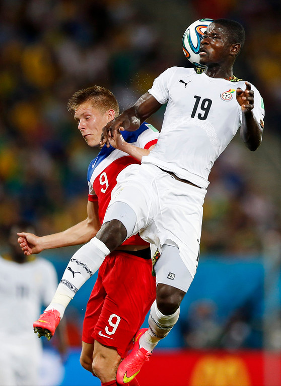 Description of . Ghana's Jonathan Mensah, right, goes up over United States' Aron Johannsson to head the ball during the group G World Cup soccer match between Ghana and the United States at the Arena das Dunas in Natal, Brazil, Monday, June 16, 2014. (AP Photo/Julio Cortez)