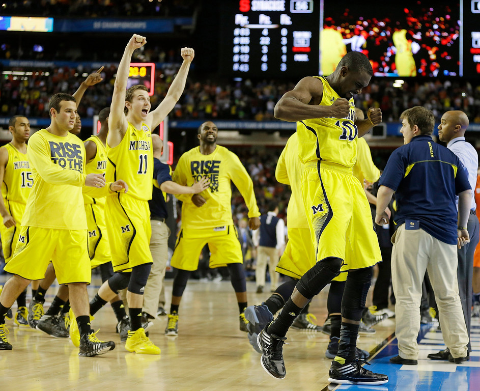 Description of . Michigan players react after the second half of the NCAA Final Four tournament college basketball semifinal game against Syracuse, Saturday, April 6, 2013, in Atlanta. Michigan won 61-56. (AP Photo/Charlie Neibergall)