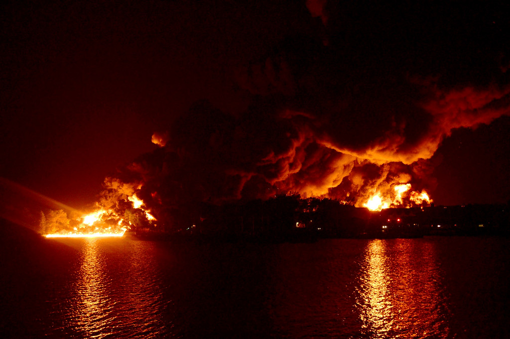 Description of . The town continues to burn following a train derailment and explosion in Lac Megantic, Quebec, early July 6, 2013. The train was hauling about 50,000 barrels of crude from North Dakota's Bakken shale development to Irving Oil's 300,000 barrel per day (bpd) plant in Saint John, New Brunswick.  REUTERS/Jean Gauthier