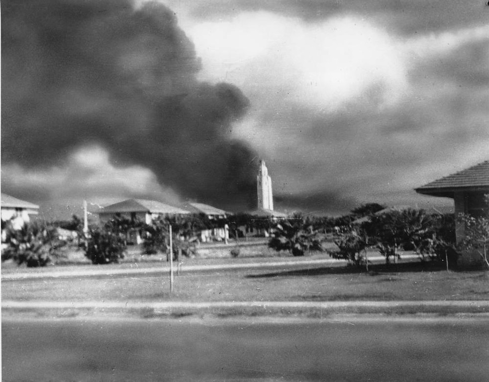 Description of . A column of black smoke rises from the U.S. Navy base in Pearl Harbor, Oahu, Hawaii at 7:55 a.m., Sun., Dec. 7, 1941 as Japan declared war against the United States.  Bombs exploding over