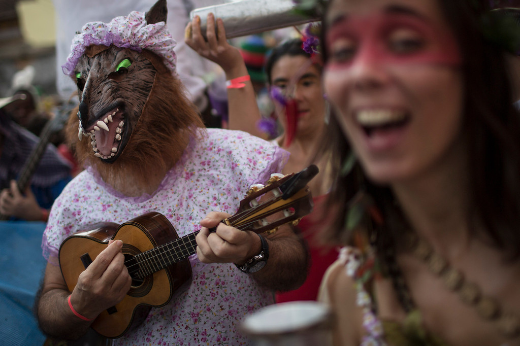 "Description of . Dressed as The Big Bad Wolf from the fairytale Little Red Riding Hood, a reveler strums a cavaquinho, a small four-stringed guitar, at the Heaven on Earth block party during Carnival celebration in Rio de Janeiro, Brazil, Saturday, March 1, 2014. Rio\'s over-the-top Carnival is the highlight of the year for many local residents. Hundreds of thousands of merrymakers will take to the streets in the nearly 500 open-air ""Bloco\"" parties. (AP Photo/Felipe Dana)"
