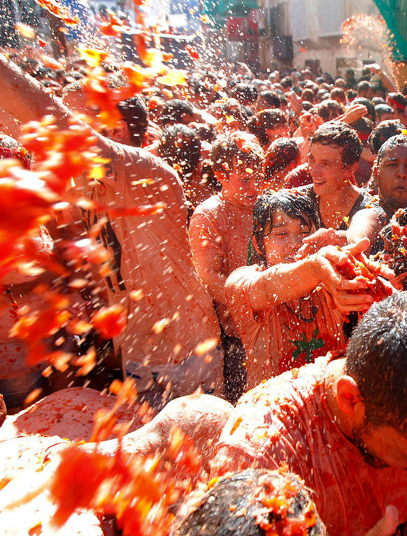 Description of . Crowds of people throw tomatoes at each other during the annual
