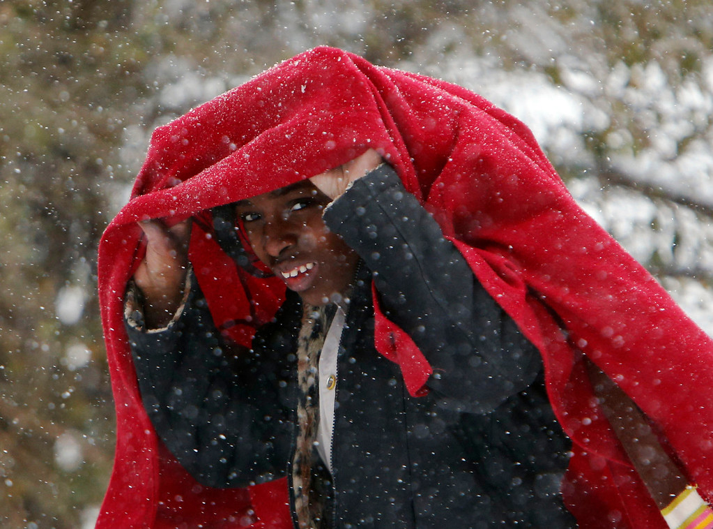 Description of . Maya Tilley covers her head from the blowing snow as she  walks home from school in Childersburg, Ala. Tuesday Jan. 28, 2014. A fast-moving, unexpectedly severe winter storm blanketed much of Alabama with a treacherous layer of frozen precipitation Tuesday.  (AP Photo/Hal Yeager)