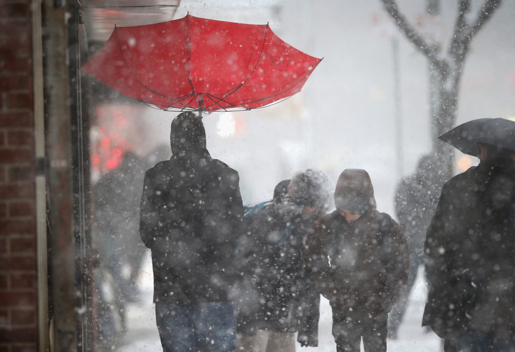 Description of . A person walks with an upturned umbrella during a snowstorm on February 13, 2014 in New York City. Heavy snow and high winds made for a hard morning commute in the city.  (Photo by John Moore/Getty Images)