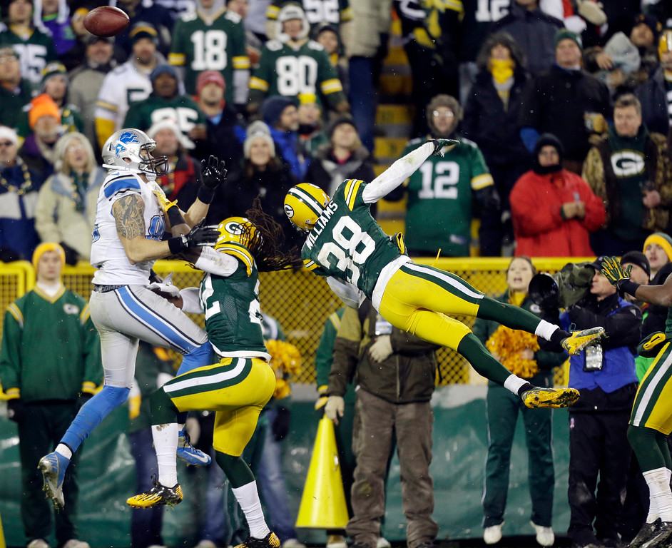 Description of . Green Bay Packers' Tramon Williams (38) and Jerron McMillian (22) break up a pass intended for Detroit Lions' Tony Scheffler during the second half of an NFL football game Sunday, Dec. 9, 2012, in Green Bay, Wis. The Packers won 27-20. (AP Photo/Jeffrey Phelps)