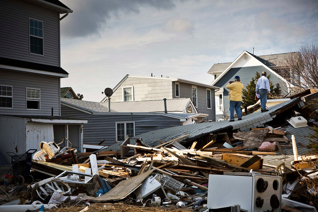 Description of . Men survey damage caused by Hurricane Sandy in the Ortley Beach area of Toms River, New Jersey November 28, 2012. The storm made landfall along the New Jersey coastline on October 29. REUTERS/Andrew Burton OCIETY)