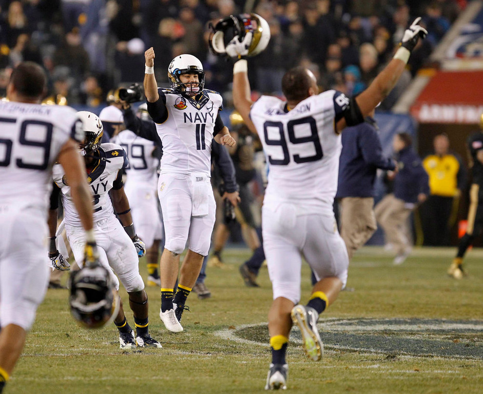 . Navy players Pablo Beltran (11) and Wes Henderson (99) celebrate a win over Army at the conclusion of the Army versus Navy NCAA football game in Philadelphia, Pennsylvania, December 8, 2012. REUTERS/Tim Shaffer