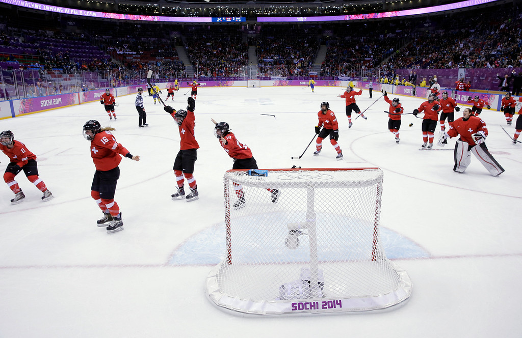 Description of . Switzerland players react after winning the women's bronze medal ice hockey game against Sweden at the 2014 Winter Olympics, Thursday, Feb. 20, 2014, in Sochi, Russia. Switzerland won 4-3. (AP Photo/David J. Phillip )