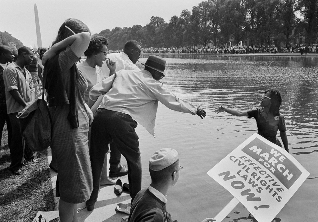 Description of . Kathleen Johnson of Newark, N.J. gets help from unidentified members of the crowd assembled near the Lincoln Memorial as part of the March On Washington, Aug. 28, 1963. Mrs. Johnson fell into the reflecting pool near the memorial while trying to take a photograph of the area.  (AP Photo)