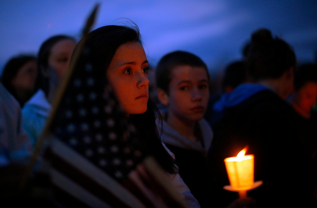 """Description of . Local residents attend a candlelight vigil in the Dorchester neighborhood of Boston, Massachusetts April 16, 2013 where eight-year-old Boston Marathon explosion victim Martin Richard lived. A Little League baseball player, Martin lived in the blue Victorian house in working-class Dorchester - a Boston neighborhood dotted with \""""Kids at Play\"""" traffic signs and budding trees - with his parents Bill and Denise, sister Jane, 7, and brother Henry, 10. Bill Richard told the world in an email on Tuesday that his son had been killed when bombs exploded at the marathon finish line. Martin\'s mother and sister were seriously injured.   REUTERS/Brian Snyder"""