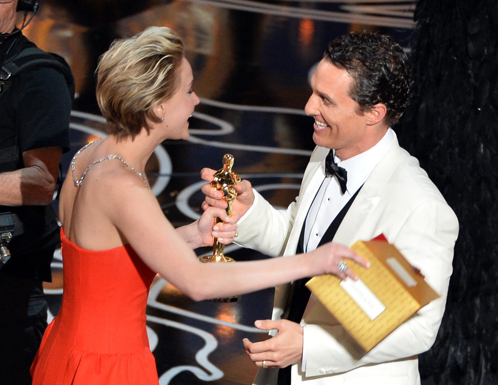 Description of . Actor Matthew McConaughey (R) accepts the Best Performance by an Actor in a Leading Role award for 'Dallas Buyers Club' from actress Jennifer Lawrence (L) onstage during the Oscars at the Dolby Theatre on March 2, 2014 in Hollywood, California.  (Photo by Kevin Winter/Getty Images)