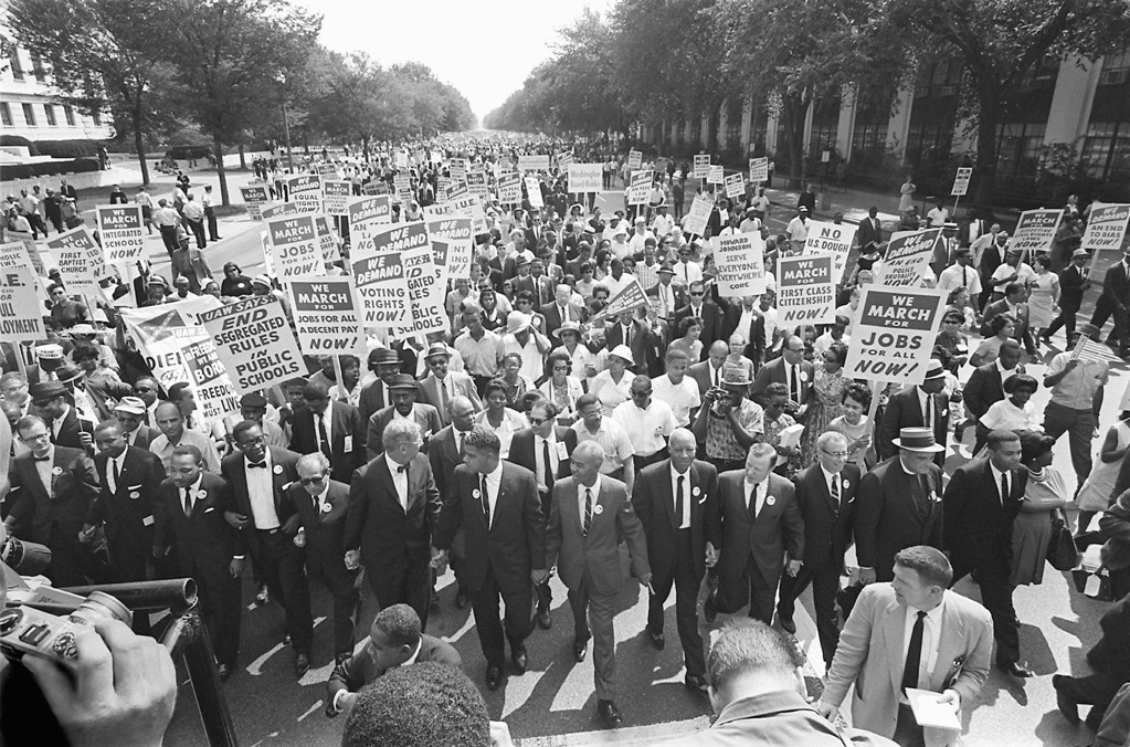 Description of . The clergyman and civil rights leader Martin Luther KIng (3rd from left) and other black and white civil right leaders march 28 August 1963 on the Mall in Washington DC during the