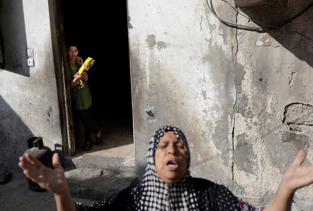 Description of . Palestinian Heygar Jendiyah, gestures as she speaks to the photographer, while her daughter Ranin, 10, stands background, at the house, partially destroyed by an Israeli strike earlier during the war, in the Sabra neighborhood of Gaza City, northern Gaza Strip, Thursday, July 31, 2014. The building houses 21 members of the extended family, and now with several rooms destroyed, they try to go about their lives, without electricity and without running water for several hours a day. (AP Photo/Lefteris Pitarakis)