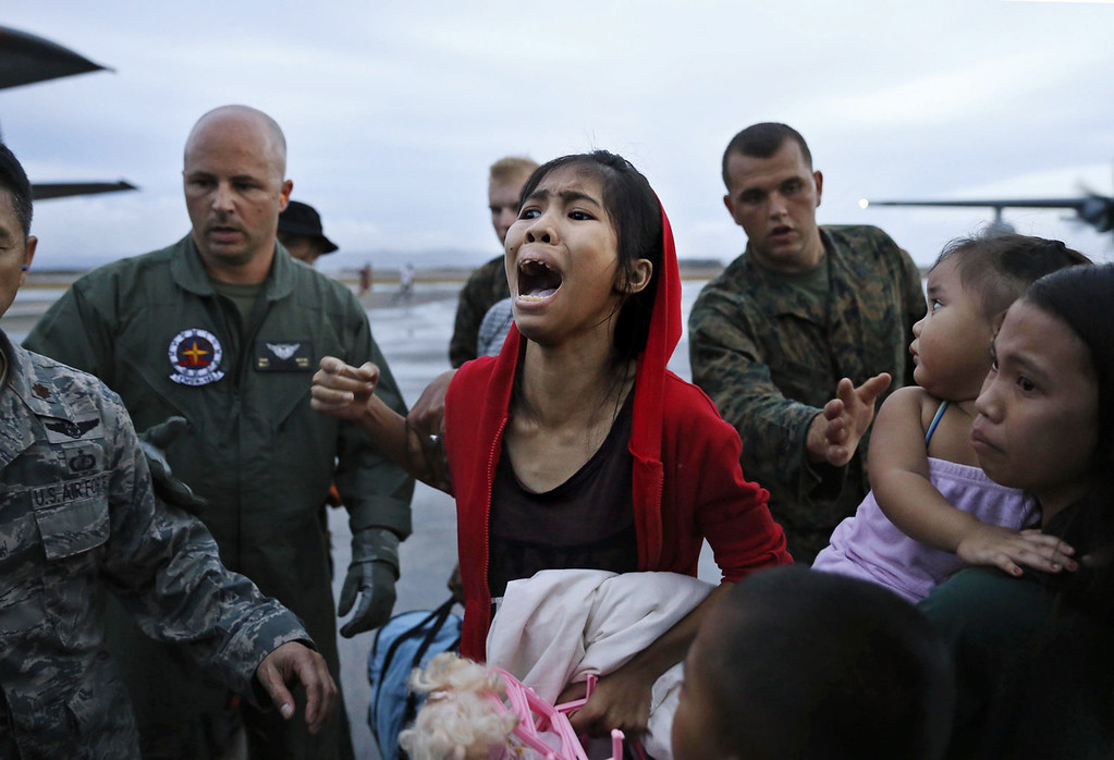 Description of . An evacuee cries for a relative while boarding a US military evacuation flight at the airport in Tacloban in the aftermath of Typhoon Haiyan on November 12, 2013 in Tacloban, Leyte, Philippines. Typhoon Haiyan, packing maximum sustained winds of 195 mph (315 kph), slammed into the southern Philippines and left a trail of destruction in multiple provinces, forcing hundreds of thousands to evacuate and making travel by air and land to hard-hit provinces difficult. Around 10,000 people are feared dead in the strongest typhoon to hit the Philippines this year. (Photo by Kevin Frayer/Getty Images)