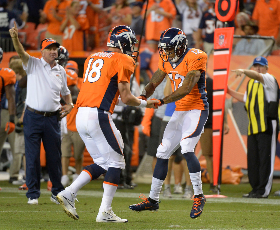Description of . Denver Broncos wide receiver Andre Caldwell (12) celebrates a touchdown with Denver Broncos quarterback Peyton Manning (18).  (Photo by John Leyba/The Denver Post)