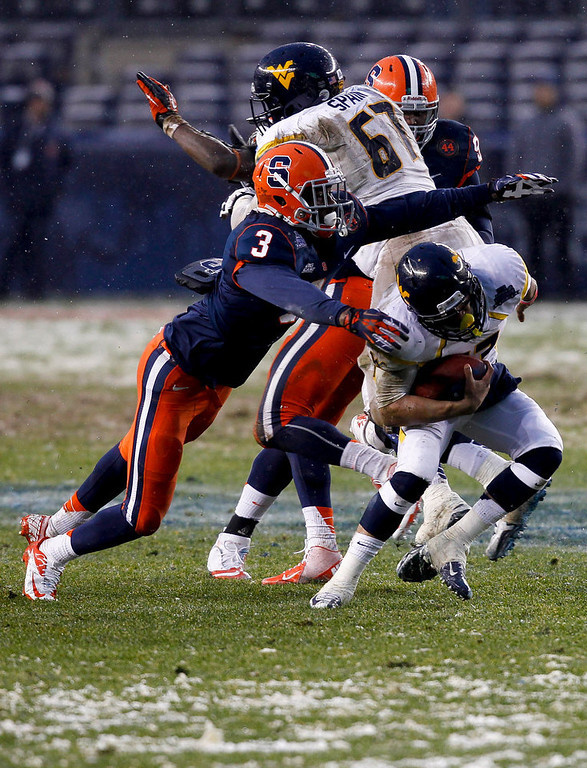 Description of . Stedman Bailey #3 of the West Virginia Mountaineers dodges Durell Eskridge #3 of the Syracuse Orange in the New Era Pinstripe Bowl at Yankee Stadium on December 29, 2012 in the Bronx borough of New York City.  (Photo by Jeff Zelevansky/Getty Images)