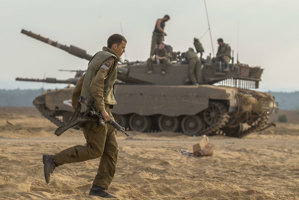 Description of . An Israeli soldier runs in front of an Israeli Merkava tank at an army deployment area on the southern Israeli border with the Gaza Strip, on August 1, 2014. Israeli forces in the southern Gaza Strip are searching for a missing soldier they fear may have been captured by militants at the start of a new ceasefire, the army said. AFP PHOTO / JACK GUEZ/AFP/Getty Images