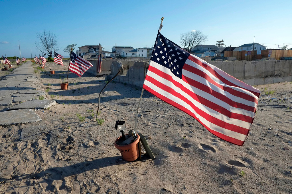Description of . Flags mark the empty lots where beach cottages used to be in the Breezy Point section of the Queens borough of New York on Thursday, July 4, 2013. More than 110 homes were destroyed by fire in Breezy Point last October caused by Superstorm Sandy. (AP Photo/Mark Lennihan)
