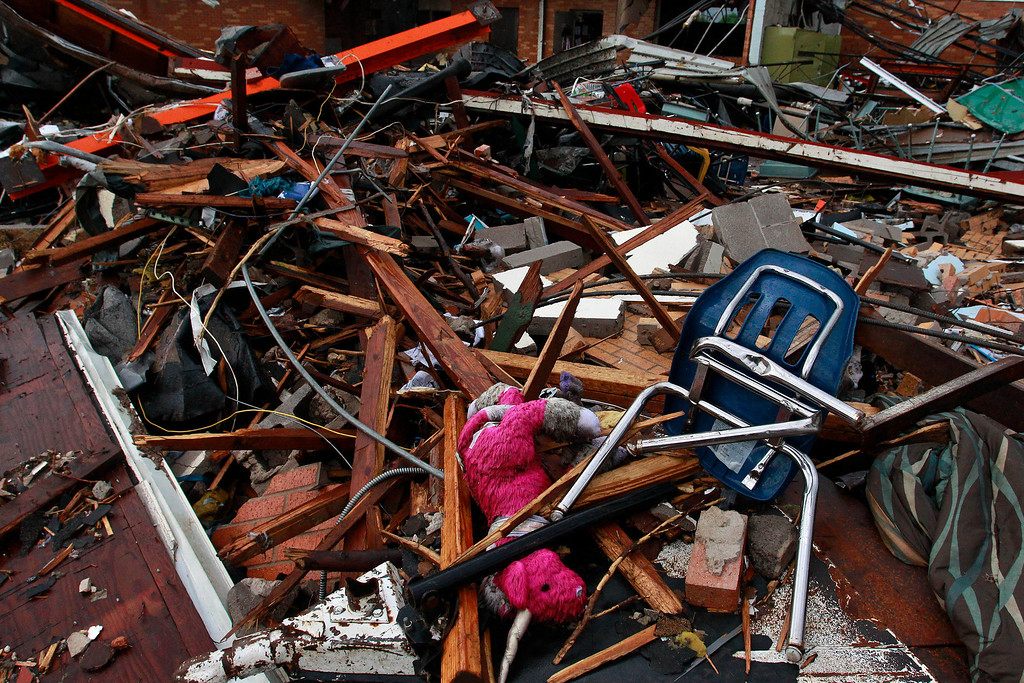 Description of . A stuffed pink unicorn is tangled amid the wreckage of Plaza Towers Elementary, where seven children were killed earlier in the week when a tornado hit Moore, Okla., Thursday, May 23, 2013. The huge tornado roared through the Oklahoma City suburb Monday, flattening entire neighborhoods and destroying the elementary school with a direct blow as children and teachers huddled against winds up to 200 mph. (AP Photo/Brennan Linsley)