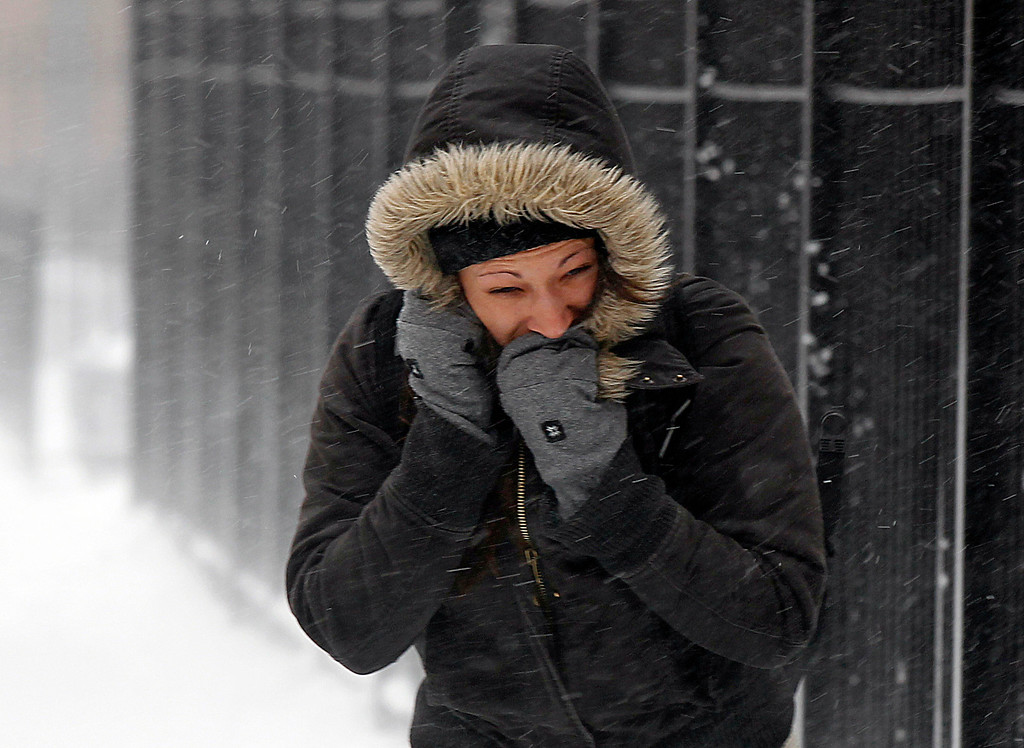 Description of . A commuter walks against blowing snow Wednesday, Feb. 5, 2014, in Chicago. Heavy, blowing snow is moving across much of Illinois as the state gets pelted by the latest round of winter weather. (AP Photo/Kiichiro Sato)