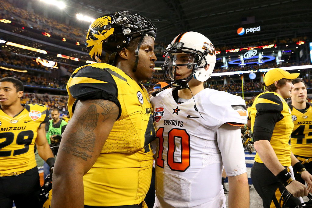 Description of . ARLINGTON, TX - JANUARY 03:  Kony Ealy #47 of the Missouri Tigers and Clint Chelf #10 of the Oklahoma State Cowboys walk into each other after the Tigers defeat the Cowboys 41-31 during the AT&T Cotton Bowl on January 3, 2014 in Arlington, Texas.  (Photo by Ronald Martinez/Getty Images)
