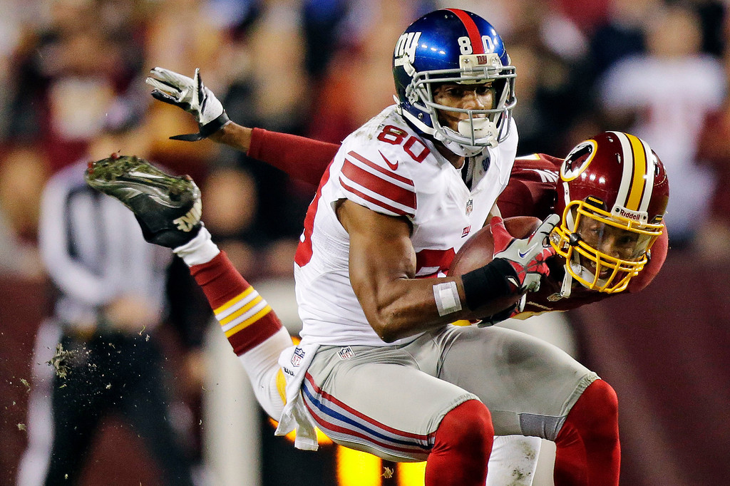 Description of . New York Giants wide receiver Victor Cruz (80) pulls in a pass under pressure from Washington Redskins defensive back Cedric Griffin during the first half of an NFL football game in Landover, Md., Monday, Dec. 3, 2012. (AP Photo/Evan Vucci)