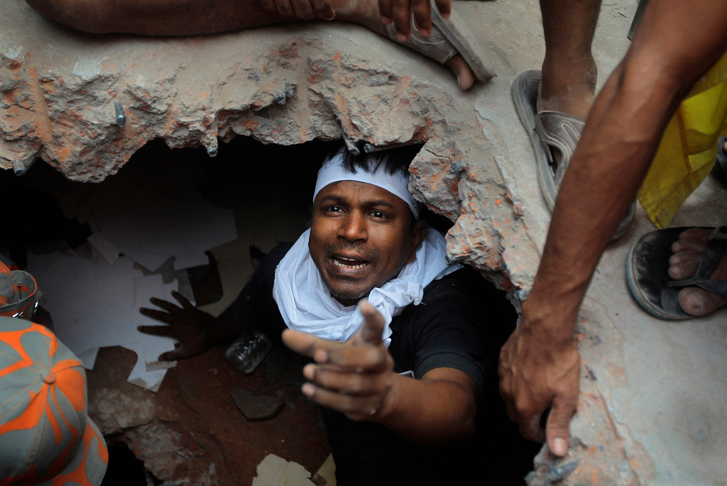 Description of . A Bangladeshi rescuer looking for survivors gestures from beneath a concrete slab of a building that collapsed  Wednesday in Savar, near Dhaka, Bangladesh,Thursday, April 25, 2013. (AP Photo/A.M.Ahad)