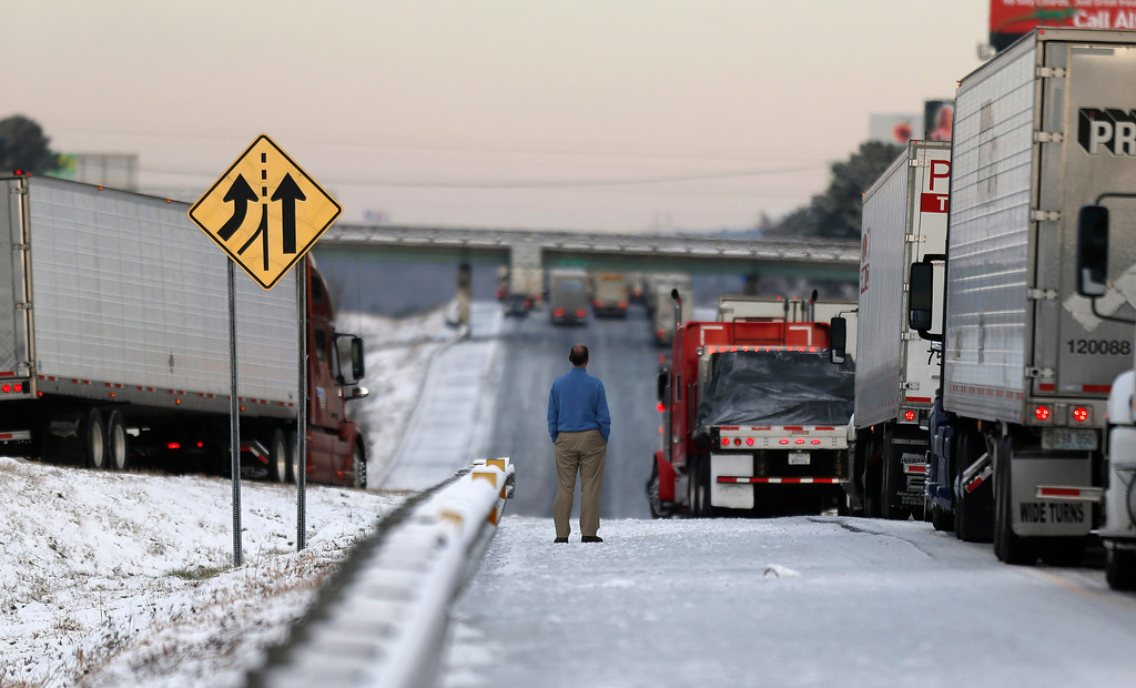 Description of . A man stands on the frozen roadway as he waits for traffic to clear along Interstate 75 Wednesday, Jan. 29, 2014, in Macon, Ga. A winter storm dumped snow and covered parts of the state with ice.  Gov. Nathan Deal said early Wednesday that the National Guard was sending military Humvees onto Atlanta's snarled freeway system in an attempt to move stranded school buses and get food and water to people. (AP Photo/John Bazemore)