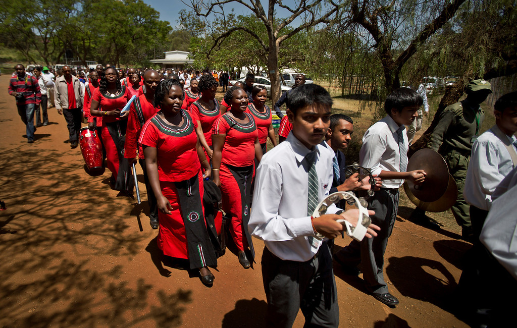 Description of . Members of a choir and junior band lead a procession at a memorial service and tree-planting marking the one-month anniversary of the the Sept. 21 Westgate Mall terrorist attack, in Karura Forest in Nairobi, Kenya Monday, Oct. 21, 2013.  (AP Photo/Ben Curtis)