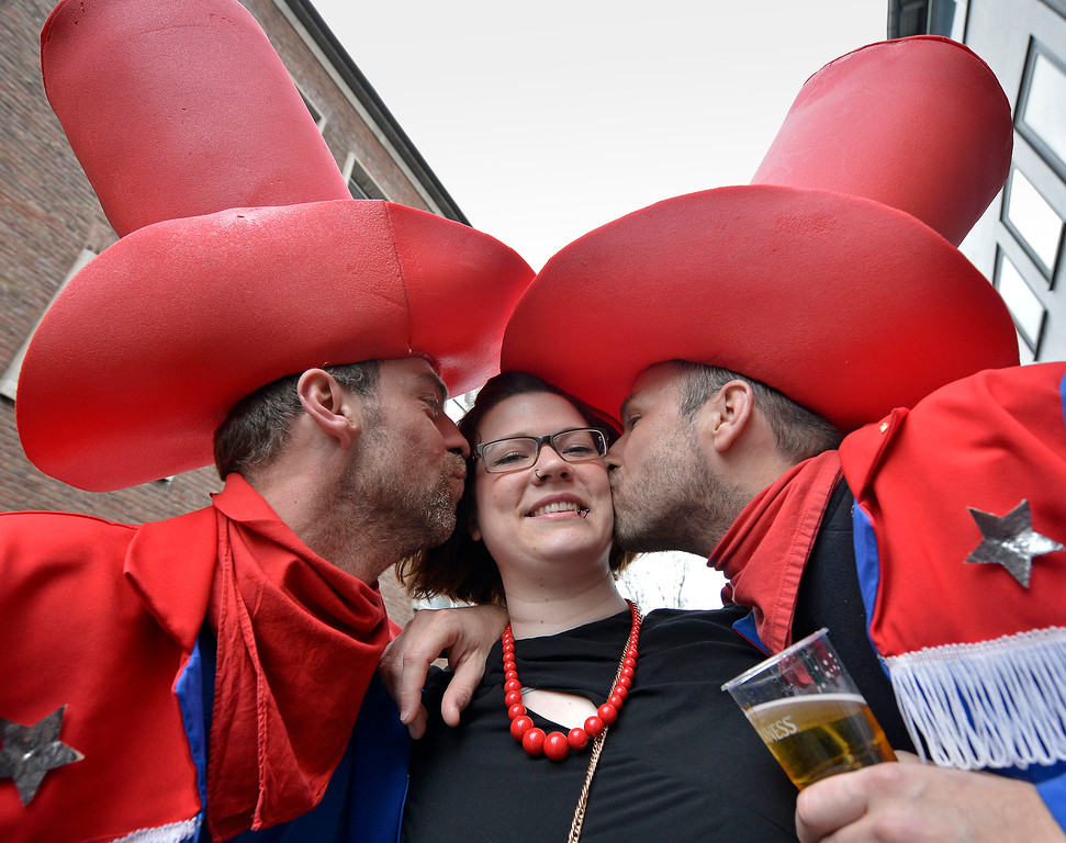 "Description of . Two men kiss a girl on the street when tens of thousands revelers dressed in carnival costumes celebrate the start of the street-carnival on the so called ""Old Women\'s Day\"" in the party capital Cologne, Germany, Thursday, Feb. 27, 2014. (AP Photo/Martin Meissner)"