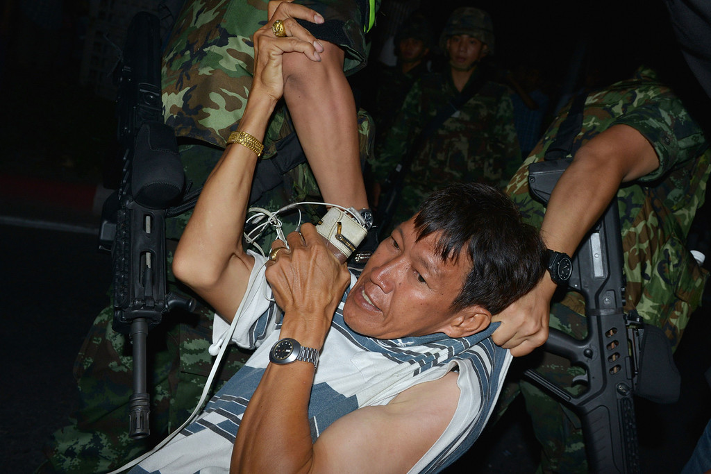 Description of . A protester is dragged away by Thai army soldiers while taking part in anti-coup rally on May 23, 2014 in Bangkok, Thailand. Anti-coup protesters rallied in Bangkok\'s shopping district, a day after the military seized control in a bloodless coup. Minor scuffles broke out during the rally and at least 4 protesters were detained by the army. Martial law imposes a 10pm to 5am curfew and bans public assembly. (Photo by Rufus Cox/Getty Images)