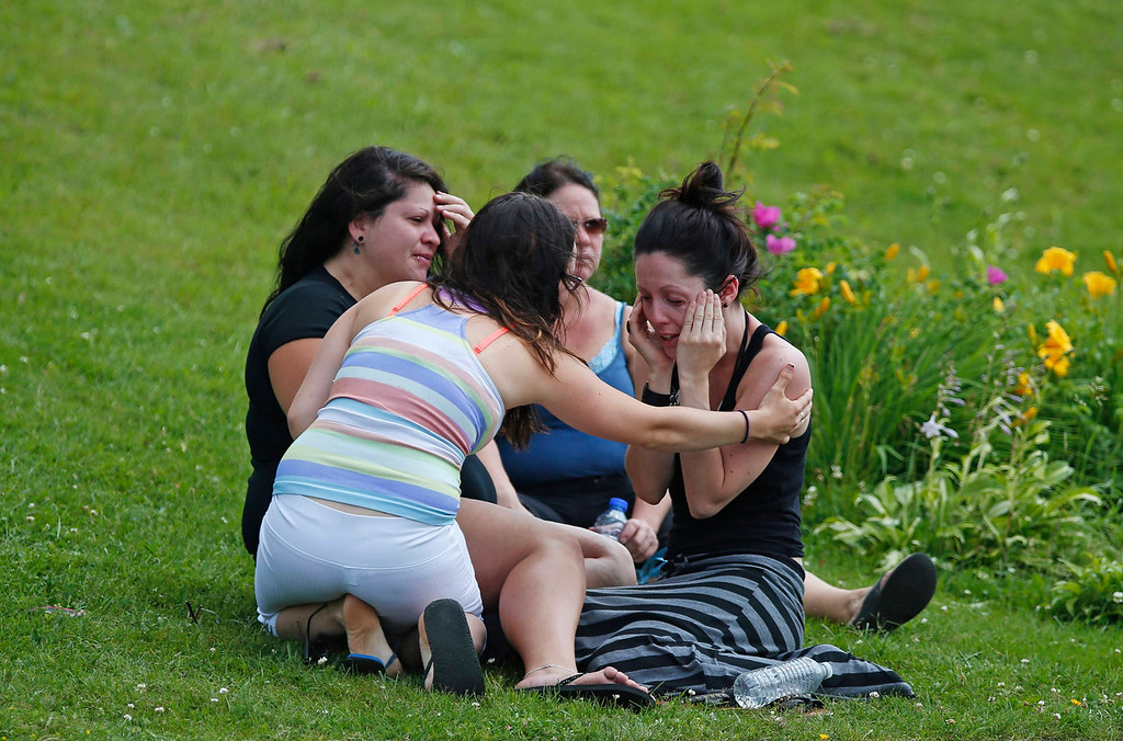 Description of . A woman comforts her friend while they sit on the grass at the Polyvalente Montignac, the school sheltering the people who were forced to leave their houses after the explosion, in Lac Megantic, July 7, 2013. Several people were missing after four tank cars of petroleum products exploded in the middle of a small town in the Canadian province of Quebec early on Saturday in a fiery blast that destroyed dozens of buildings.  REUTERS/Mathieu Belanger