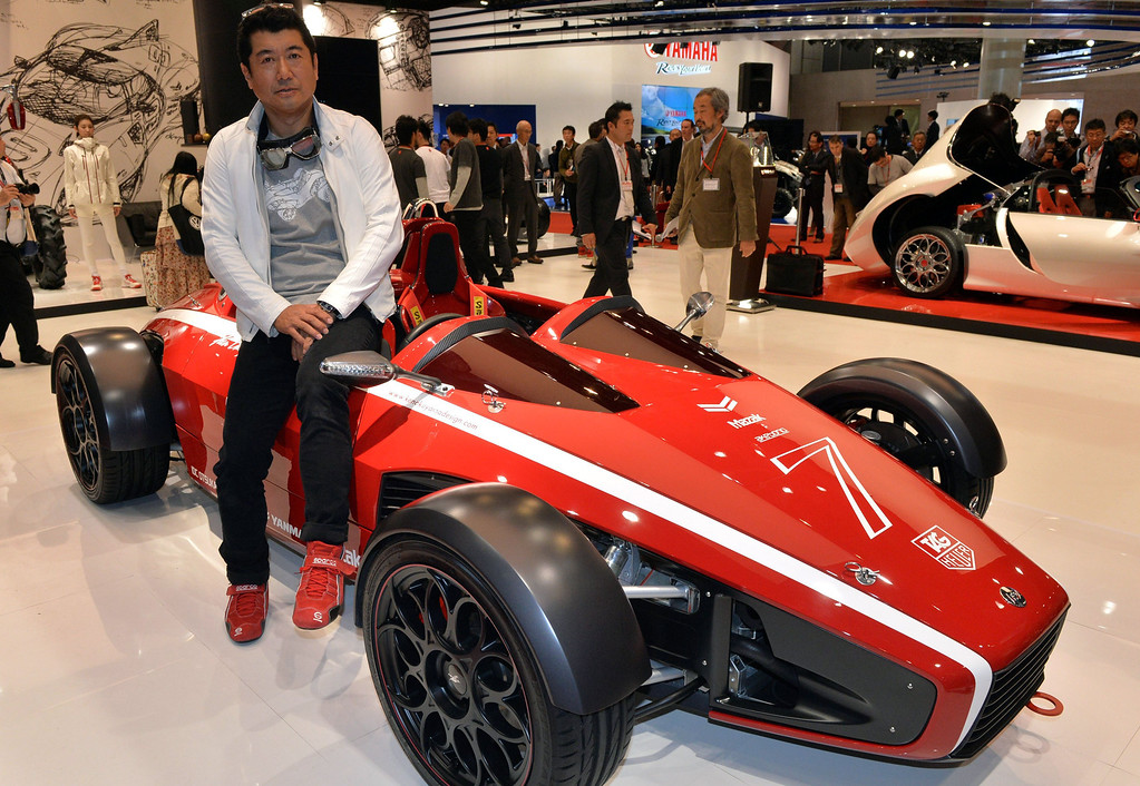 Description of . Japanese car designer Ken Okuyama, who designed a Ferrari car, displays the formula car designed